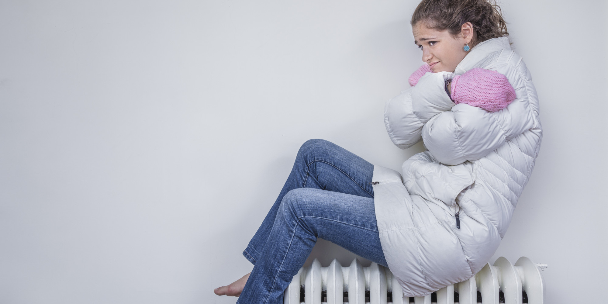 Teen girl sitting on a radiator